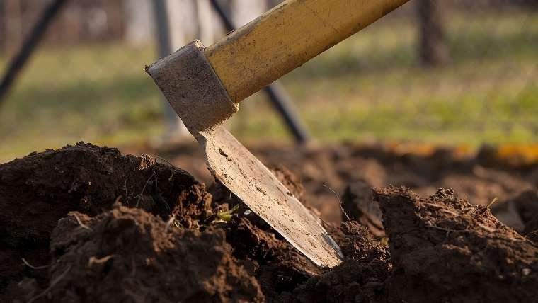 鍬で土を耕す
